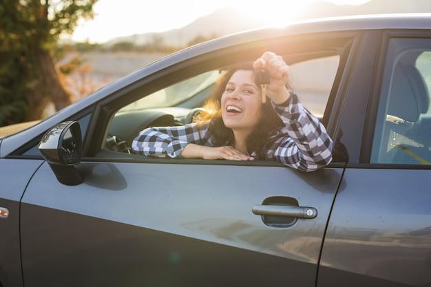 Nieuw auto-, aankoop- en bestuurdersconcept - jonge vrouw die sleutel in een auto toont.