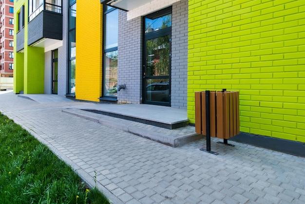 Nieuw baksteen gekleurd woongebouw met meerdere verdiepingen op de achtergrond van een blauwe hemel met een zonnige schittering
