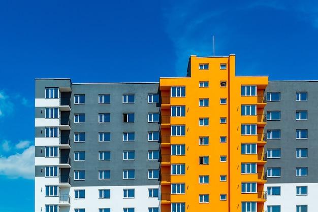 Nieuw blok van moderne appartementen met balkons en blauwe lucht op de achtergrond