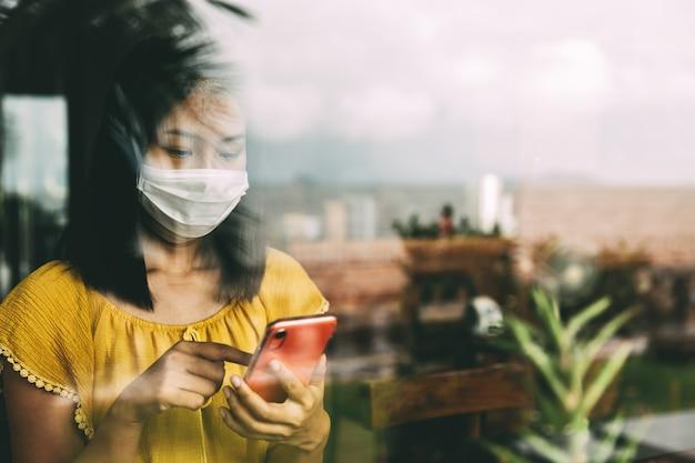 Nieuw concept voor normale levensstijlmensen, aziatische reiziger met masker die mobiele telefoon gebruikt in coffeeshopcafé als gevolg van het uitbreken van coronavirus covid-19 in thailand