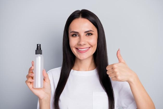 Nieuw effectief antibacterieel product tegen het coronavirus. portret van positief meisje aanwezig gezonde hygiëne-object advertenties goedkeuren duim omhoog teken dragen witte t-shirt geïsoleerde grijze kleur achtergrond