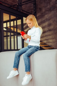 Nieuw gadget. geconcentreerd blond meisje zittend op de bank en online chatten met haar vriend