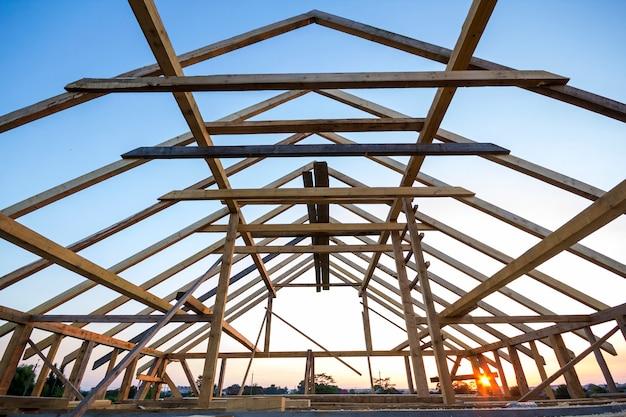 Nieuw houten huis in aanbouw. close-up van het dakframe van de zolder tegen duidelijke hemel van binnenuit. ecologisch droomhuis van natuurlijke materialen. bouwen, bouwen en renoveren concept.