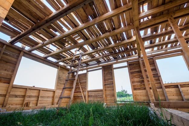 Nieuw houten huis in aanbouw. close-up van muren en plafondframe met vensteropeningen van binnenuit. ecologisch droomhuis van natuurlijke materialen. bouw-, constructie- en renovatieconcept.