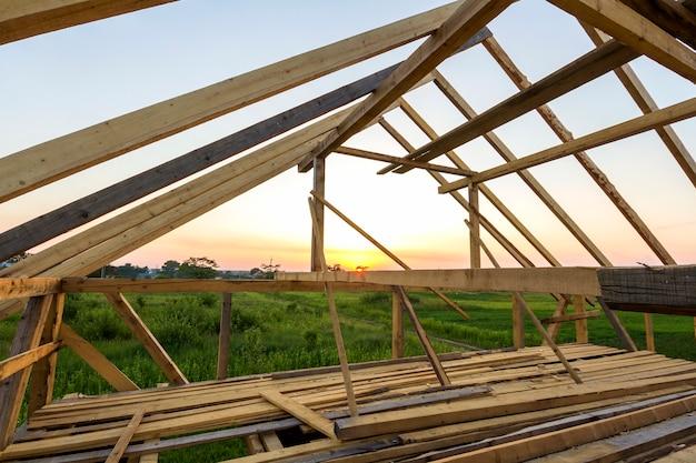 Nieuw houten huis in aanbouw. close-up van zolder dakframe tegen heldere hemel van binnenuit. ecologisch droomhuis van natuurlijke materialen. bouw-, constructie- en renovatieconcept.