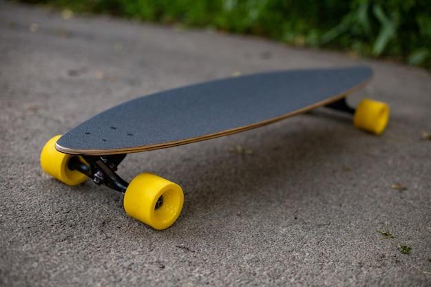 Nieuw houten pennyboard met gele wielen op het asfalt