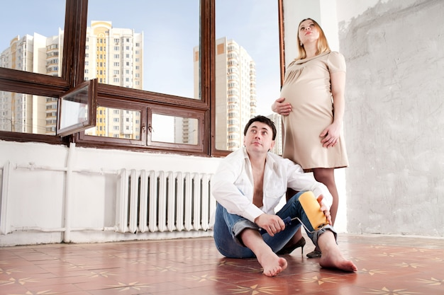 Nieuw huis. man en de zwangere vrouw in het nieuwe huis.