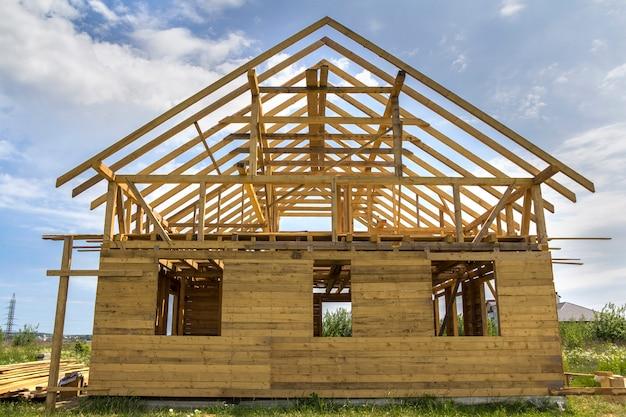 Nieuw huisje van natuurlijke ecologische houtmaterialen in aanbouw in groen veld. houten wanden en steil dakframe. vastgoed, investeringen, professioneel bouwen en wederopbouwconcept.