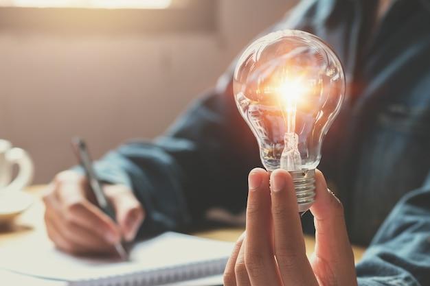 Nieuw idee en creatief concept voor de hand van de bedrijfsvrouw die gloeilamp houden