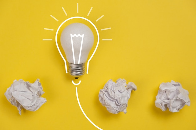 Nieuw ideeconcept met verfrommeld bureaudocument en witte gloeilamp op gele achtergrond. creatieve oplossing tijdens brainstormsessieconcept. plat lag, bovenaanzicht, kopie ruimte