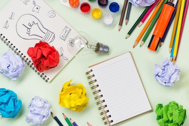 Nieuw ideeconcept met verfrommeld kantoorpapier en gloeilamp