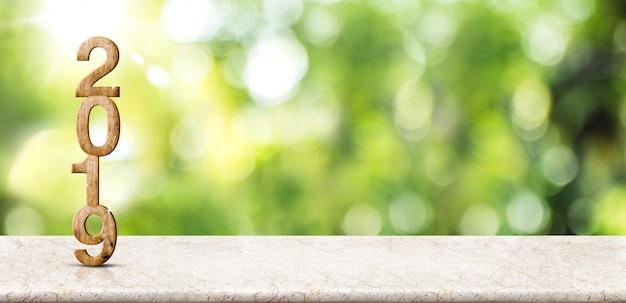 Nieuw jaar 2019 op marmeren lijst bij onduidelijk beeld abstracte groene bokeh met zonstraalachtergrond