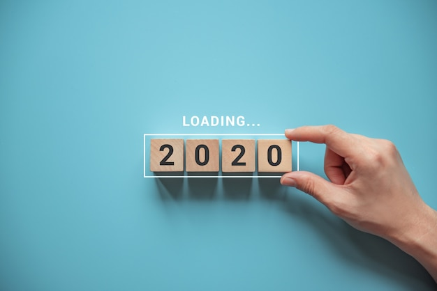 Nieuw jaar 2020 laden met hand die houten kubus in voortgangsbalk zet.