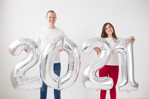 Nieuw jaar 2021 komt eraan - gelukkige jonge man en vrouw houden binnen zilverkleurige cijfers.
