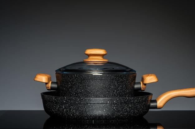 Nieuw kookgerei op zwarte achtergrond, vooraanzicht