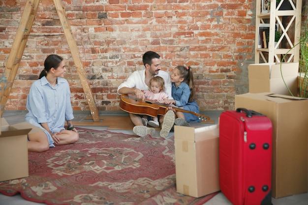 Nieuw leven. volwassen gezin verhuisde naar een nieuw huis of appartement. echtgenoten en kinderen zien er gelukkig en zelfverzekerd uit. verhuizen, relaties, lifestyle concept. dozen met hun spullen uitpakken, samen spelen.