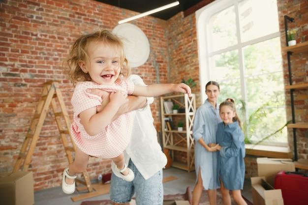 Nieuw leven. volwassen gezin verhuisde naar een nieuw huis of appartement. echtgenoten en kinderen zien er gelukkig en zelfverzekerd uit. verhuizen, relaties, nieuw levensconcept. dozen met hun spullen uitpakken, samen spelen.