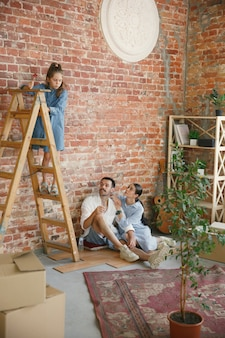 Nieuw leven. volwassen gezin verhuisde naar een nieuw huis of appartement. echtgenoten en kinderen zien er gelukkig en zelfverzekerd uit. verhuizen, relaties, nieuw levensconcept. samen spelen, zich voorbereiden op reparatie en lachen.