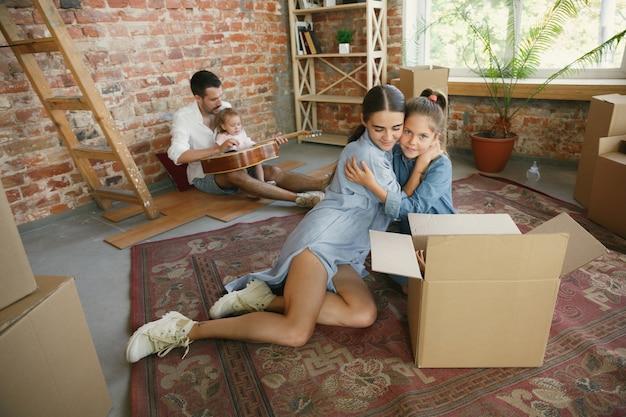 Nieuw leven. volwassen gezin verhuisde naar een nieuw huis of appartement. echtgenoten en kinderen zien er gelukkig en zelfverzekerd uit