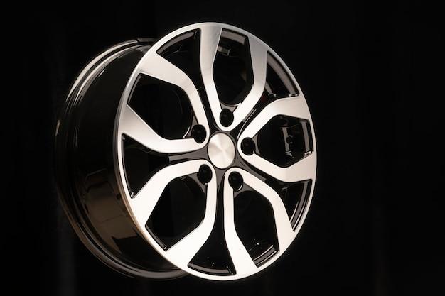 Nieuw lichtmetalen wiel van de auto, close-up op een zwarte ruimte, wielelementen, tweekleurige coating, glanzend. linker locatie op de layout
