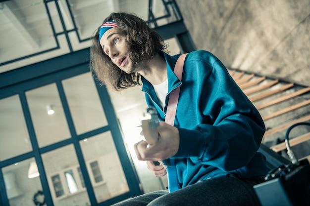 Nieuw lied maken. knappe geïnspireerde man met blauwe ogen die op een professioneel instrument optreedt terwijl hij alleen in de woonkamer is