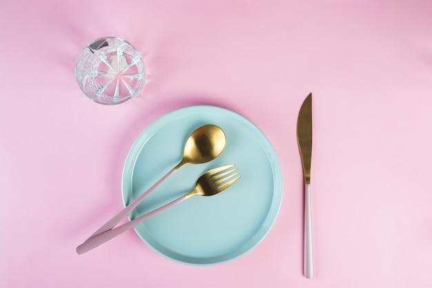 Nieuw luxe gouden bestek met glas, blauwe plaat op roze