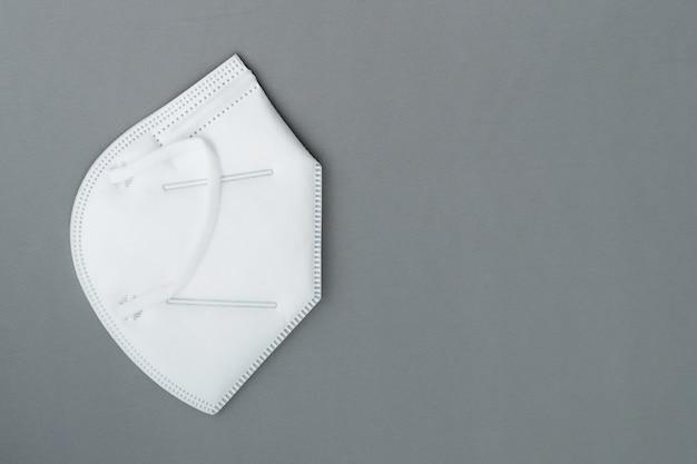 Nieuw masker kn95 op grijze achtergrond met exemplaarruimte.