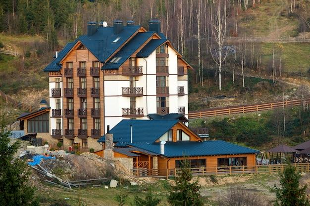 Nieuw modern comfortabel hotelgebouw van vier verdiepingen met aangrenzende gebouwen, zolderkamers en hoge schoorstenen in ecologisch landelijk gebied op sparren, lente of zomer.