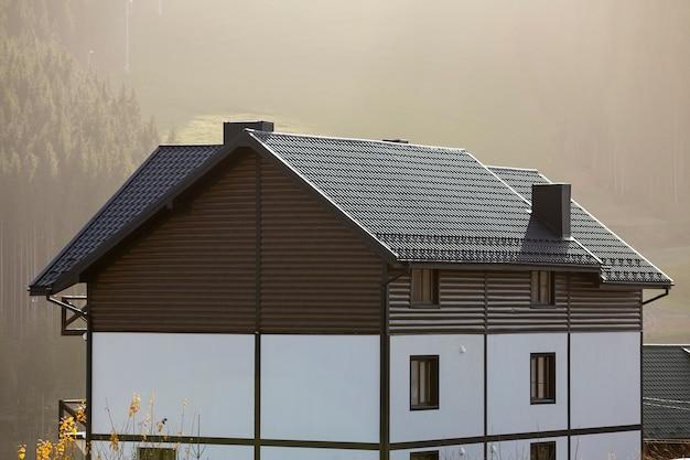 Nieuw mooi wit en bruin huisje met twee verdiepingen met schindeldak in ecologisch gebied op mistig hout en heuvelsachtergrond op zonnige de zomerdag. goed onderhouden woning, onroerend goed concept.