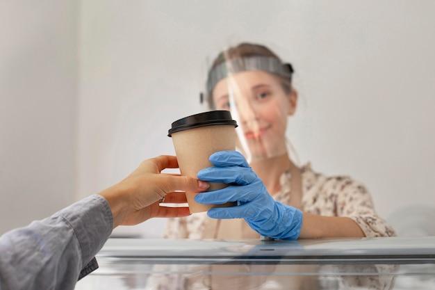 Nieuw normaal bij de coffeeshop met gezichtsscherm