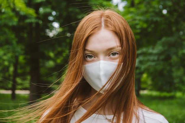 Nieuw normaal buitenportret van roodharige vrouw met beschermend masker op groene bomen backgroung young