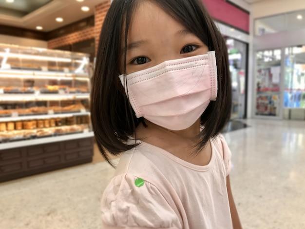 Nieuw normaal coronavirus / covid-19 is een temperatuurcontrole en screening, gelukkig aziatisch meisje draagt chirurgisch masker heeft een groene sticker om de lichaamstemperatuur in de supermarkt te controleren