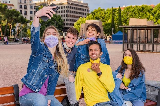 Nieuw normaal leven met het coronavirus met een jonge multiraciale groep studenten die een selfie met gezichtsmasker maakt