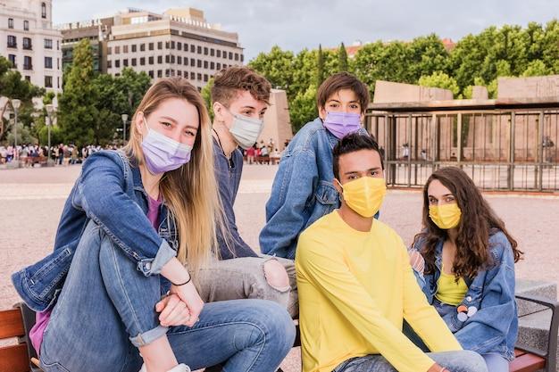 Nieuw normaal leven met het coronavirus met een jonge multiraciale groep studenten die gezichtsmasker draagt voor pandemie