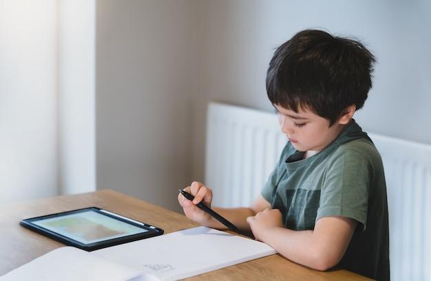 Nieuw normaal levenkind dat tablet gebruikt voor zijn huiswerk