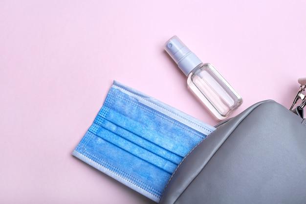 Nieuw normaal. plat lag set dames handtas met medisch gezichtsmasker en ontsmettingsmiddel spray. hygiëneproducten