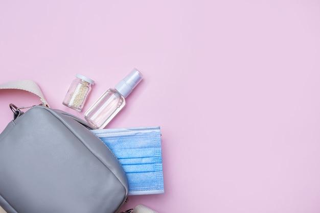 Nieuw normaal. plat lag set vrouwen handtas met medisch gezichtsmasker, ontsmettingsmiddel spray en pillen. hygiëneproducten