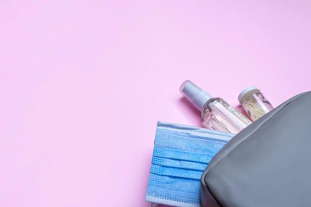 Nieuw normaal. plat lag set vrouwen handtas met medisch gezichtsmasker, ontsmettingsmiddel spray en pillen