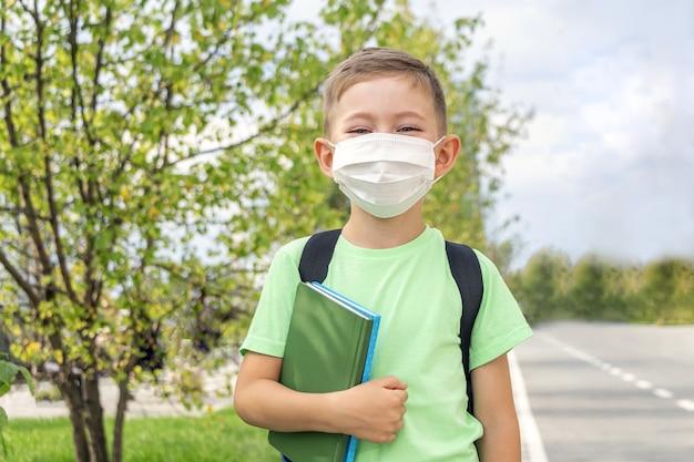 Nieuw normaal, terug naar school. schooljongen die medisch masker en rugzak draagt die leerboek in openlucht houdt