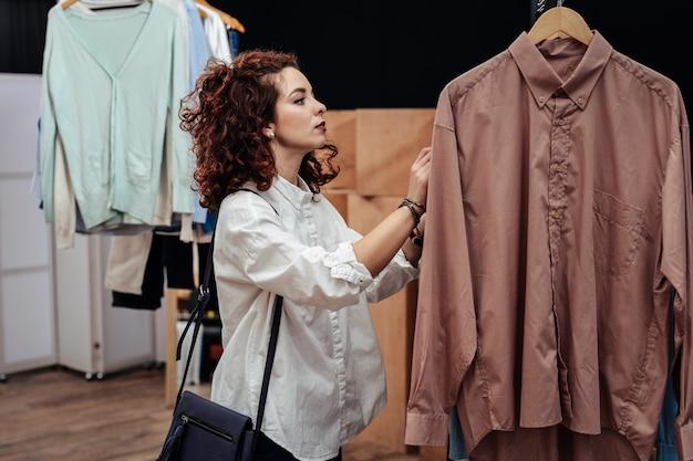Nieuw overhemd kiezen. krullende, donkerharige stijlvolle shopaholic die een wit overhemd draagt en een nieuw overhemd kiest