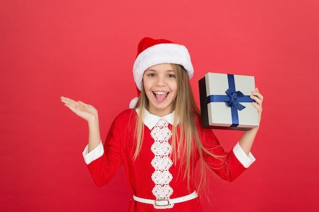 Nieuw product voor het nieuwe jaar. gelukkig meisje toont hand voor product. meisje dat product voorstelt. product promotie. kerst verkoop. rode achtergrond voor reclametekst, kopieer ruimte.