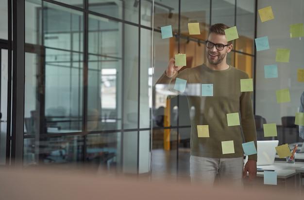 Nieuw project plannen jonge blanke man kantoormedewerker met een bril die iets op plakkerig schrijft