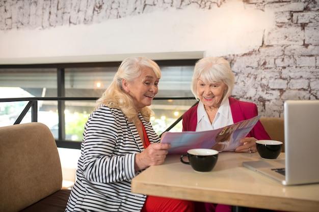 Nieuw project. twee blonde oudere dames die achter de laptop zitten en er betrokken bij kijken