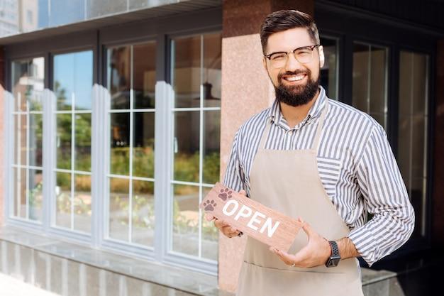 Nieuw restaurant. opgetogen vrolijke man die lacht tijdens het openen van zijn nieuwe bedrijf