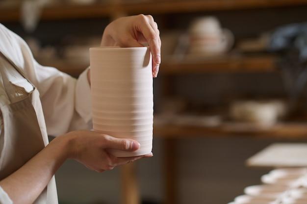 Nieuw servies. handen van een pottenbakker met een nieuw servies