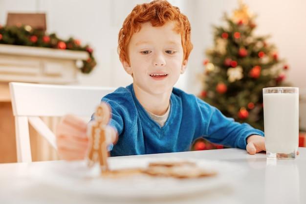 Nieuw speelgoed. selectieve aandacht voor een stralende kleine jongen die vrolijk lacht terwijl hij aan een tafel zit en met een peperkoekmannetje speelt tijdens een familieontbijt.