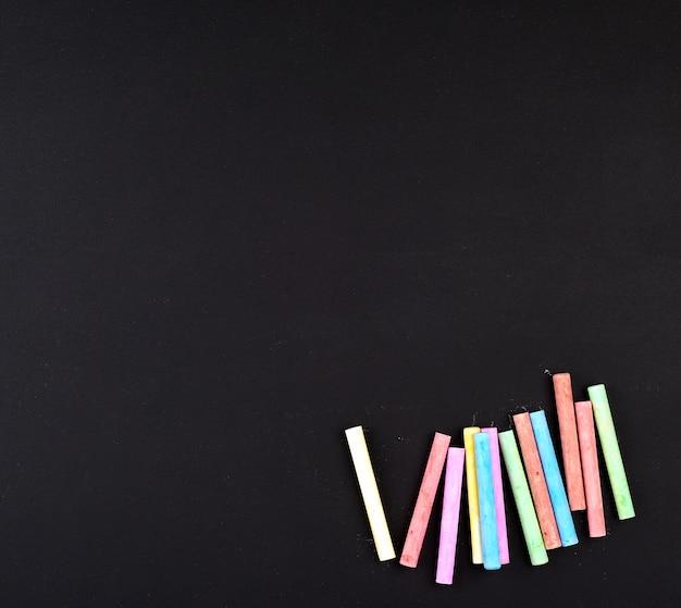 Nieuw zwart schoolbord en kleurrijk krijt, lege ruimte