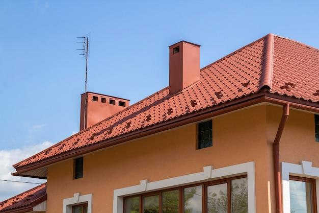 Nieuwbouw eengezinswoning met rood pannendak, kunststof ramen, gestuukte wanden en hoge schoorstenen op omheind perceel in rustige buurt. bouw en onroerend goed concept.