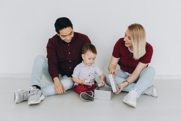 Nieuwbouw woonhuis aankoop appartement concept. multiculturele gezin met zoon zittend op de vloer, blanke moeder en aziatische vader met hun zoon