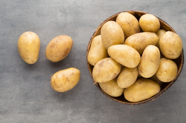 Nieuwe aardappel op de kom, grijze achtergrond.